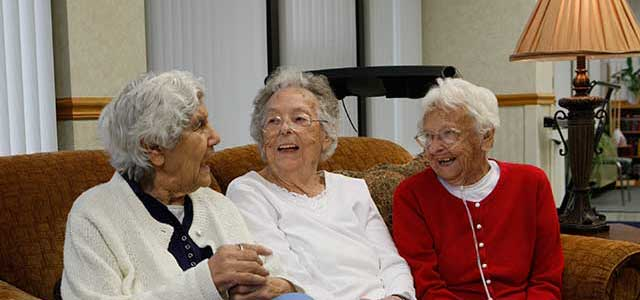Image of happy Co-op residents sitting on a couch laughing